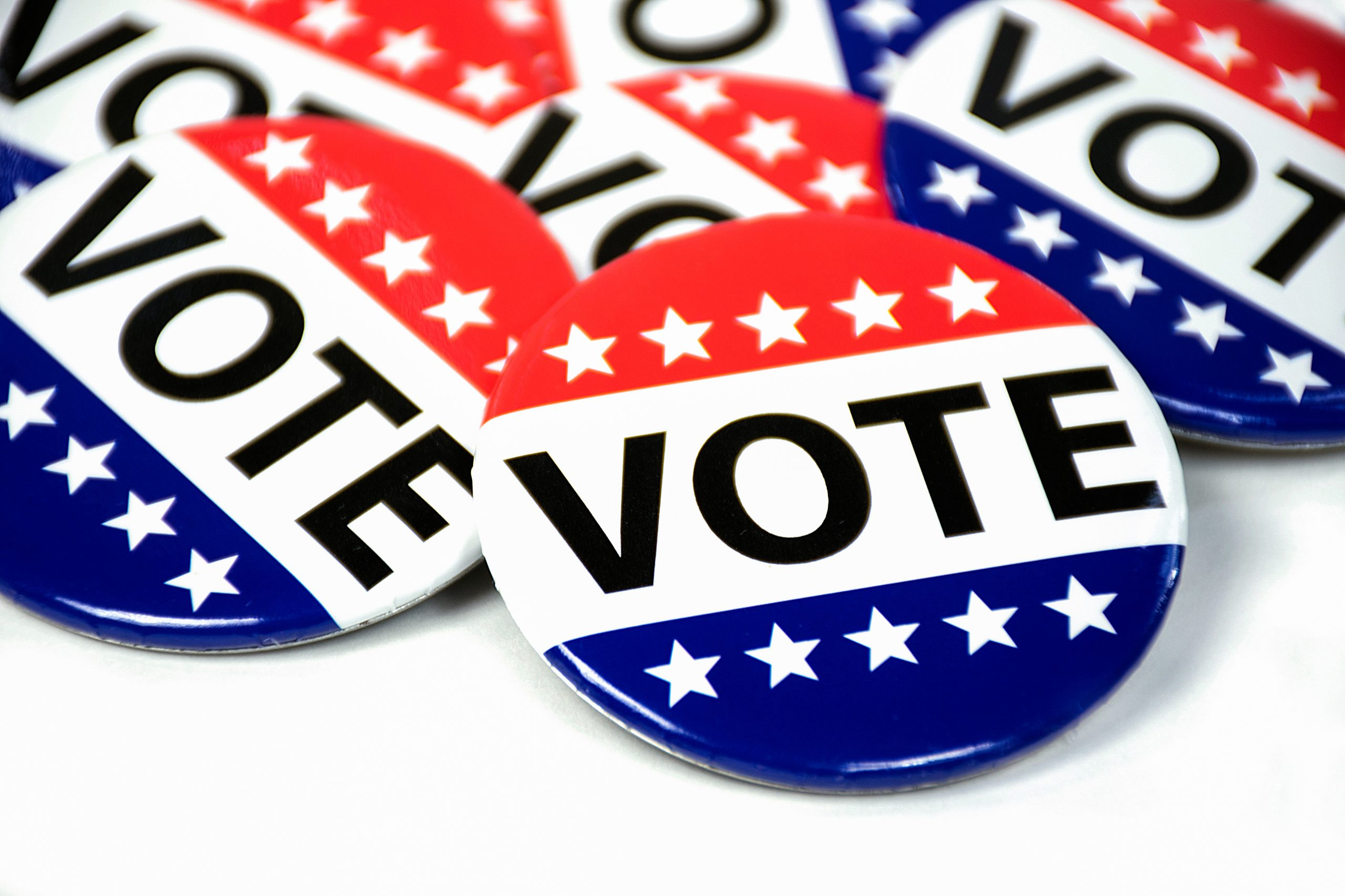 Close-up of red, white, and blue vote buttons on a white background
