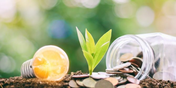 Glowing light bulb with small plant growing from soil and money coins in the glass jar against blurred natural green background with copy space for finance, saving energy and environment concept